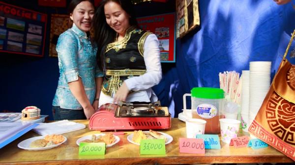 Hai nữ sinh Mông Cổ trong gian hàng với hàng loạt món ăn và quà lưu niệm.