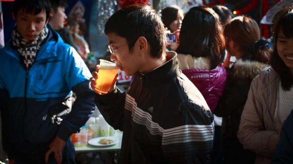 Một khách tham quan đang thưởng thức bia Séc tại gian hàng của các sinh viên CH Séc.
